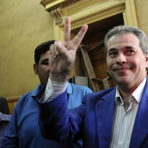 FILE - In this Saturday, Sept. 1, 2012 file photo, Tawfiq Okasha, center, a popular Egyptian TV presenter accused of inciting the killing of the country's new president on air, flashes the victory sign as he arrives for the opening of his trial, in Cairo, Egypt. Okasha has been expelled from parliament over a meeting he had with the Israeli ambassador to Egypt, which in 1979 became the first Arab nation to sign a peace treaty with Israel. (AP Photo/Mohammed Assad, File)