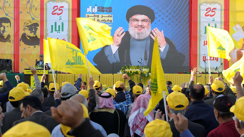 People watch Lebanon's Hezbollah leader Sayyed Hassan Nasrallah as he appears on a screen during a live broadcast to speak to his supporters at an event marking Resistance and Liberation Day,