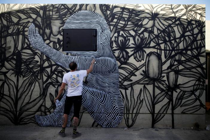 Israeli artist who goes by the name Klone, works on his wall painting during an art happening, called POW! WOW! Israel, which is connected to a week-long art and culture festival held in Hawaii called POW! WOW! Hawaii, in the southern city of Arad