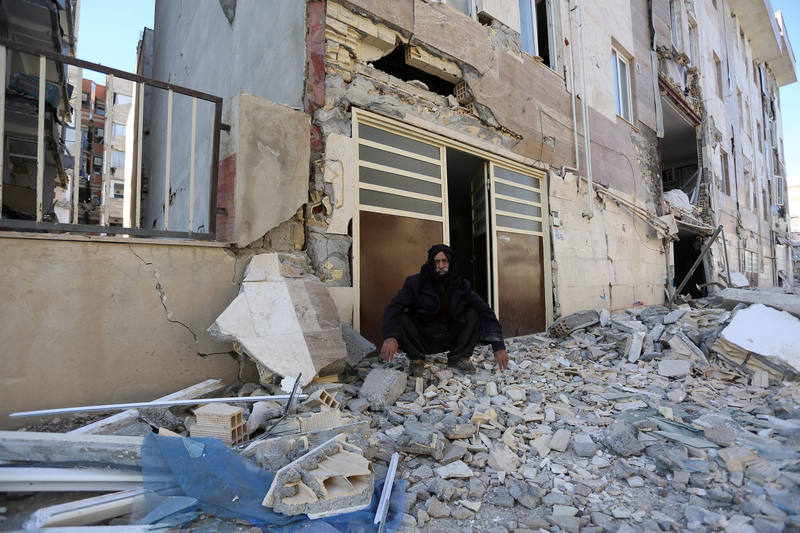 A man sits outside a damaged belonging following an earthquake in Sarpol-e Zahab county in Kermanshah