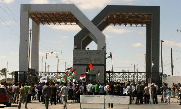 Palestinians wave a national flag and an Egyptian flag as they take part in a rally calling on Egyptian authorities to open the Rafah crossing, outside the crossing