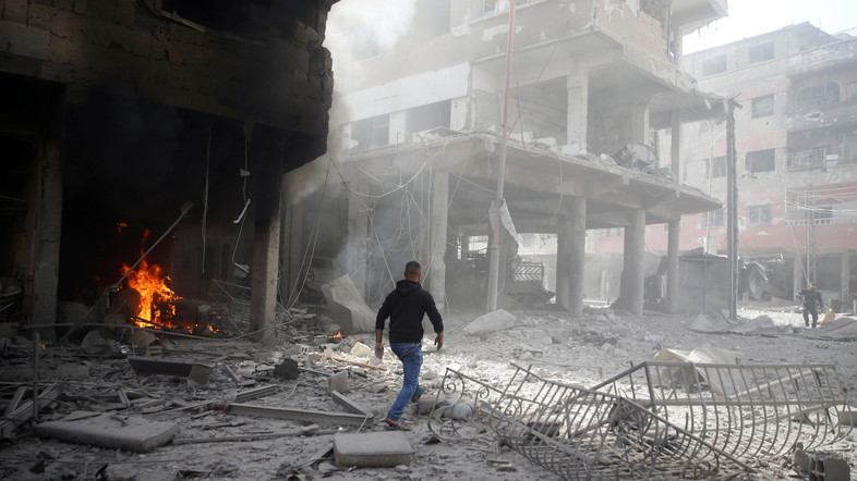A man walks on rubble at a damaged site after an airstrike in the besieged town of Douma