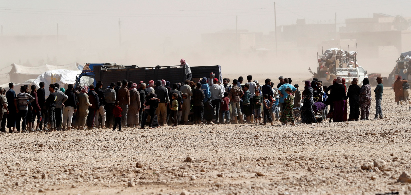 People displaced from fightings between the Syrian Democratic Forces and Islamic State militants queue for food aid from UN's World Food Programme at a refugee camp in Ain Issa