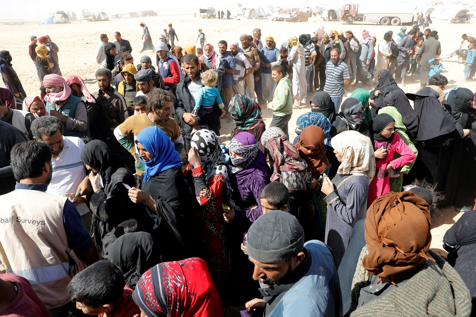 People displaced from fightings between the Syrian Democratic Forces and Islamic State militants wait for food aid from UN's World Food Programme at a refugee camp in Ain Issa