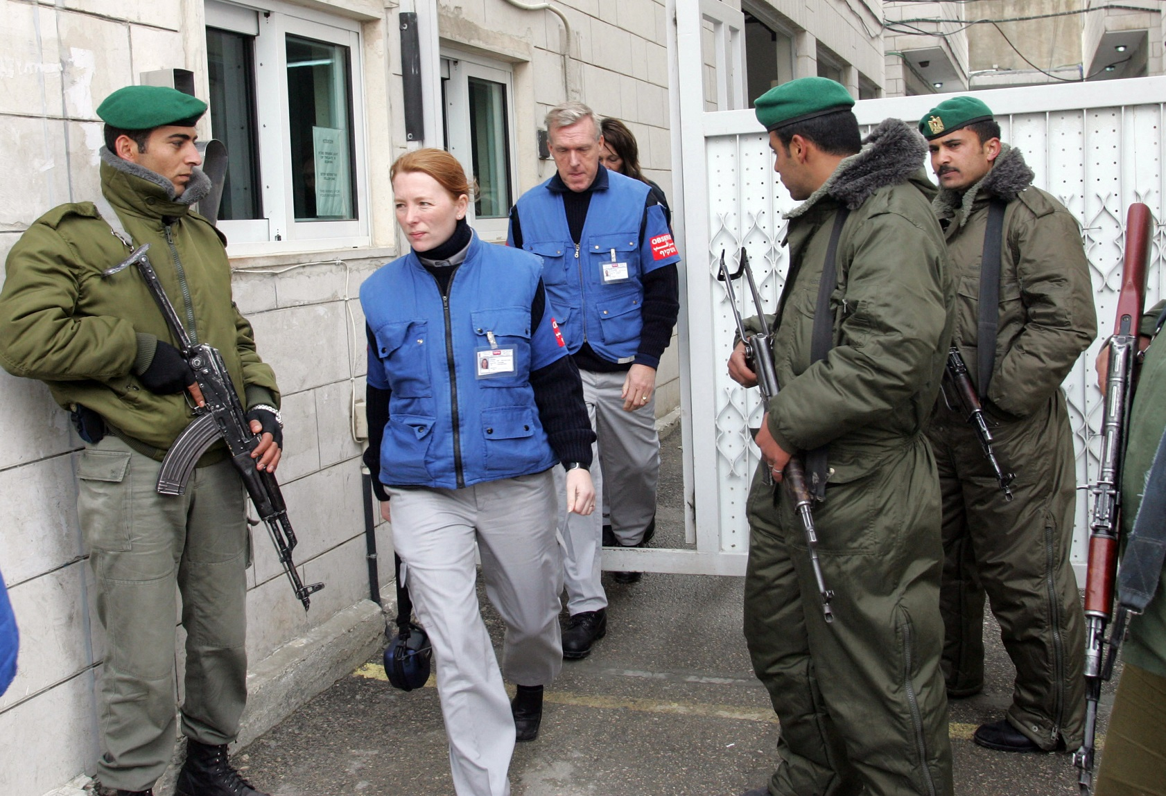 International observers from TIPH walk past Palestinian security officers in Hebron