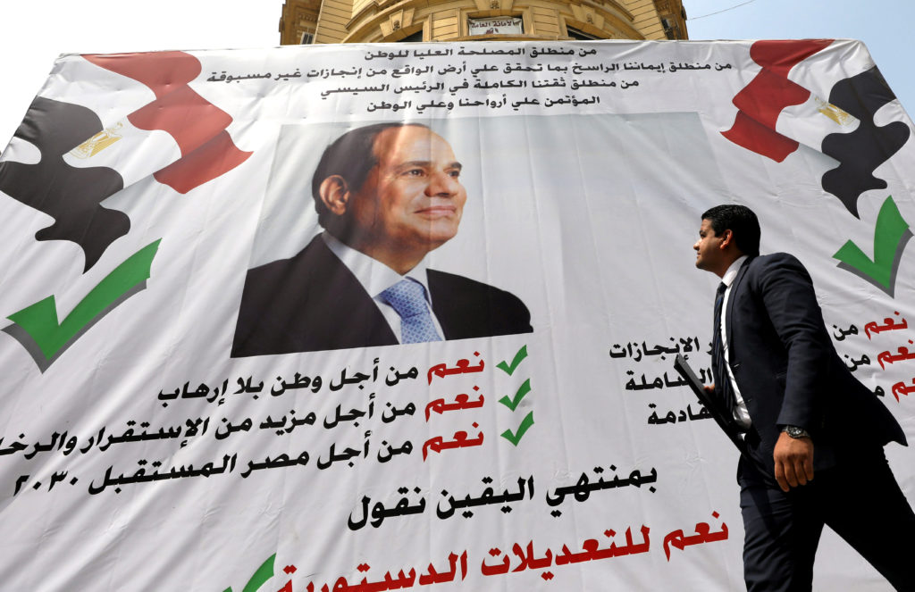A man walks in front of a banner reading, «Yes to the constitutional amendments, for a better future», with a photo of the Egyptian President Abdel Fattah al-Sisi before the approaching referendum on constitutional amendments in Cairo