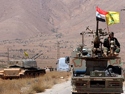 Hezbollah and Syrian flags flutter on a military vehicle in Western Qalamoun