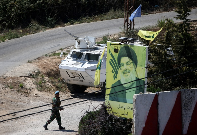 A U.N peacekeepers of the United Nations Interim Force in Lebanon (UNIFIL) walks near a poster depicting Lebanon's Hezbollah leader Sayyed Hassan Nasrallah in Adaisseh