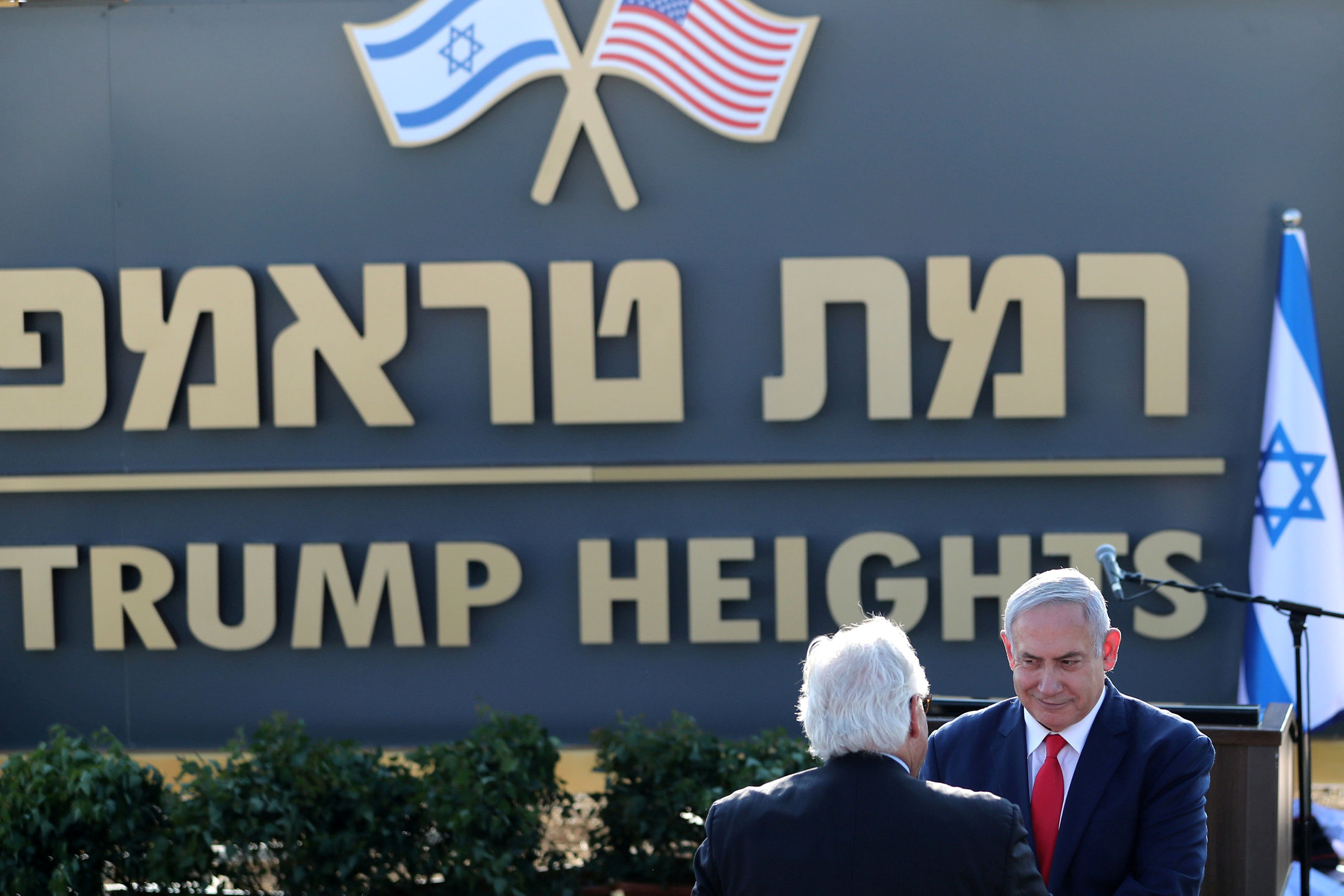 Israeli Prime Minister Benjamin Netanyahu shake hands with U.S. Ambassador to Israel David Friedman as they attend a ceremony to unveil a sign for a new community named after U.S. President Donald Trump, in the Israeli-occupied Golan Heights