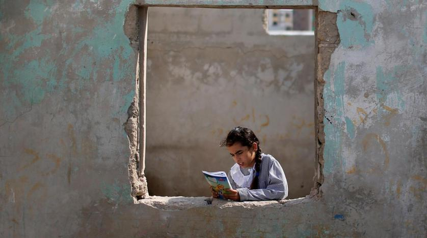 a_palestinian_unrwa_schoolgirl_holds_her_book_as_she_stands_by_a_window_outside_her_family_home_in_al-shati_refugee_camp_in_gaza_city_october_23_2019._reuters