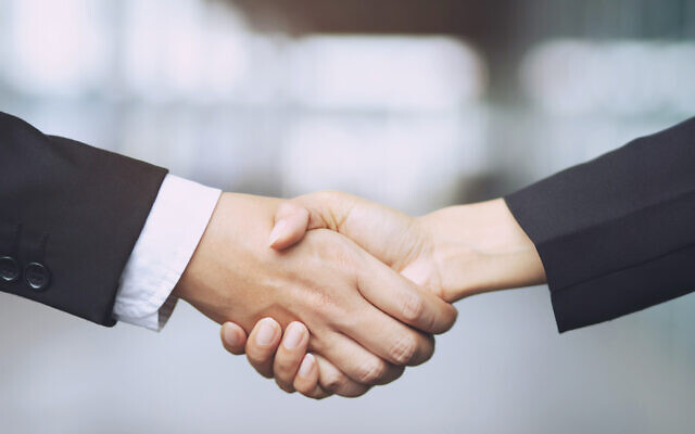 Closeup of a businessman hand shake businesswoman between two colleagues OK, succeed in business Holding hands.