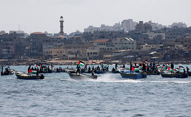 People ride boats as Palestinians prepare to sail a boat towards Europe aiming to break Israel's maritime blockade on Gaza, at the sea in Gaza