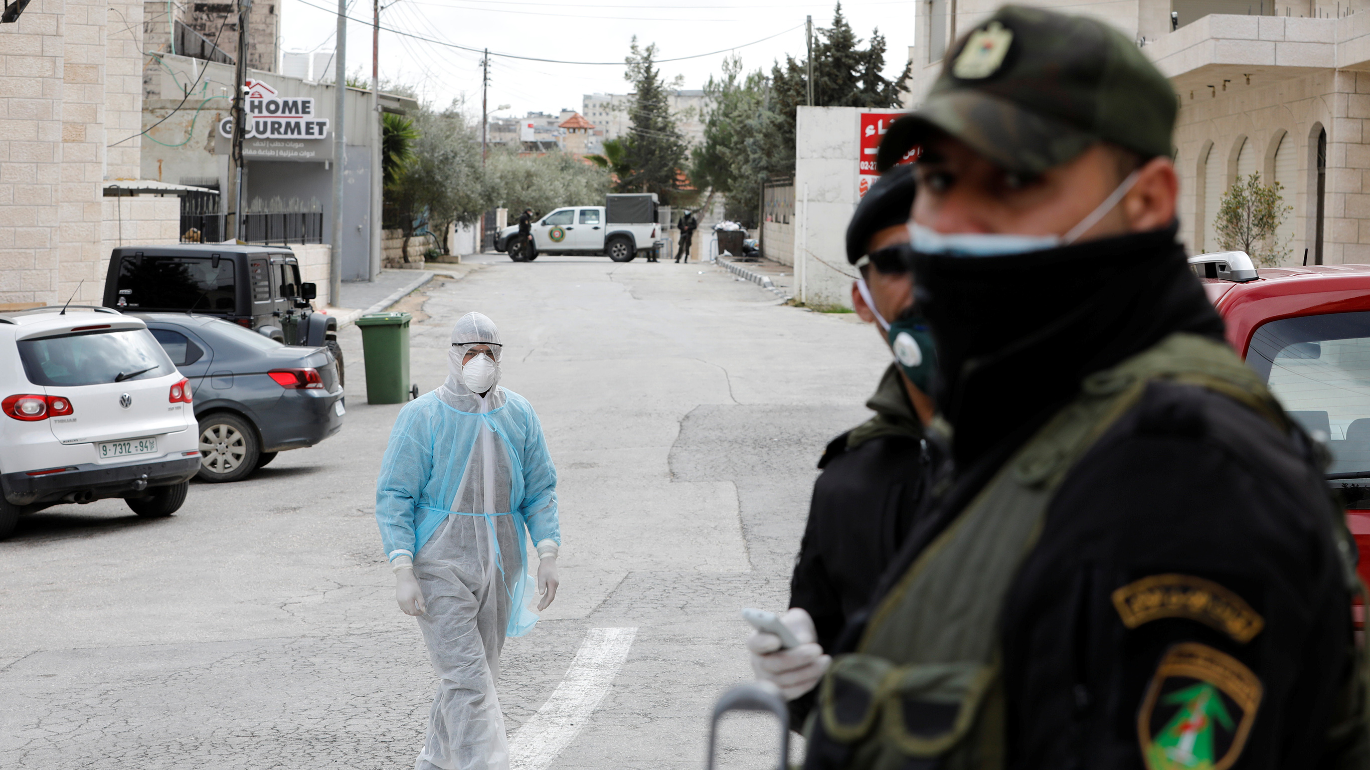 Man in a protective suit walks outside Angel Hotel in Beit Jala town in the Israeli-occupied West Bank
