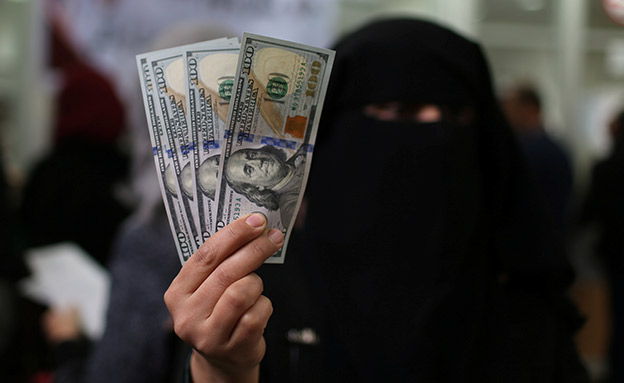 Palestinian Hamas-hired civil servant displays U.S. Dollar banknotes after receiving her salary paid by Qatar, in Khan Younis in the southern Gaza Strip