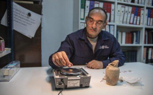5דר-רוברט-קול-מרשות-העתיקות-שוקל-את-אחד-המטבעות-שנמצאו-בפכית.-צילום-שי-הלוי-רשות-העתיקות-e1604910790781-640×400