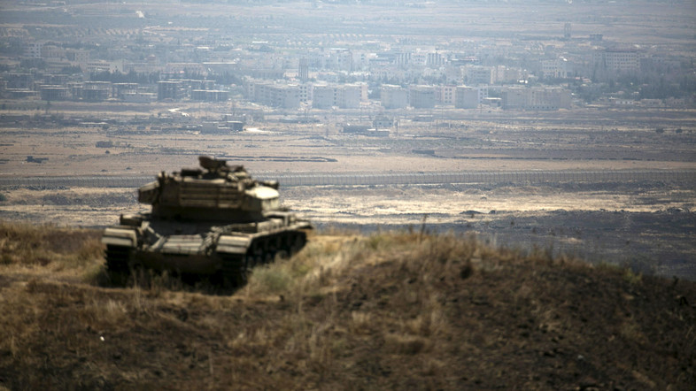 The Syrian area of Quneitra is seen in the background as an out-of-commission Israeli tank parks on a hill, near the ceasefire line between Israel and Syria, in the Israeli-occupied Golan Heights