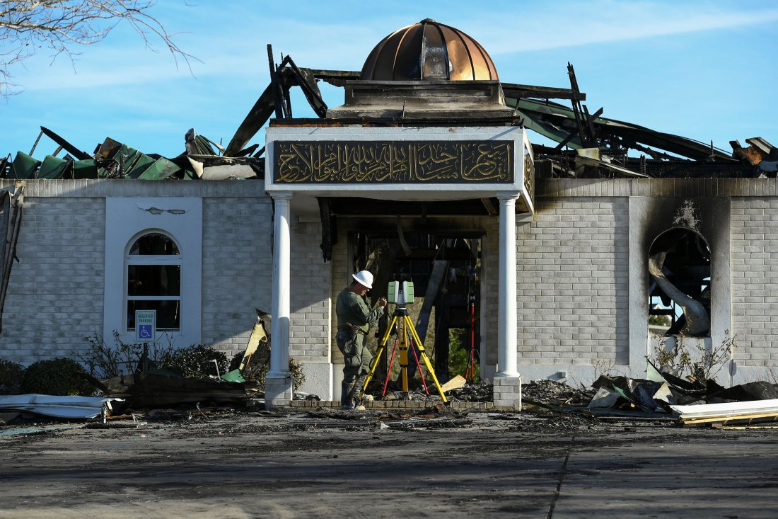 A security official investigates the aftermath of a fire at the Victoria Islamic Center mosque in Victoria, Texas